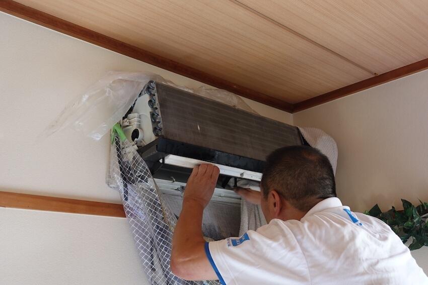 カジタク業者がエアコンをタオルで拭いている様子